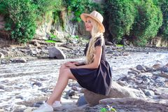 A beautiful young woman blonde with long hair in a hat sitting on a rocky shore by the river. Around the mountains royalty free stock photography
