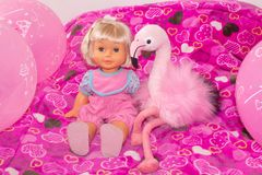 Children`s toys, baby doll and pink flamingo, gifts for children. Holiday with balloons. royalty free stock photography