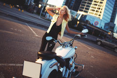 Beautiful young woman blonde standing near a motorcycle on the b Royalty Free Stock Image