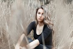 Beautiful young woman blonde in stylish jeans in a fashionable black shirt is resting royalty free stock images