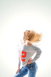 Beautiful young woman blonde in t-shirt and jeans on white backg Royalty Free Stock Photography