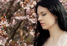 Beautiful young woman in blossom garden Stock Photography