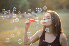 Beautiful Young Woman Blowing Bubbles Outside Royalty Free Stock Photos