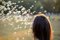 Beautiful Young Woman Blowing Bubbles Outside Royalty Free Stock Photo