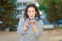 Beautiful young woman blowing confetti and having fun outdoors. royalty free stock images