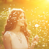Beautiful young woman blowing dandelion. Trendy young girl at s. Beautiful young woman blowing a dandelion. Trendy young girl at sunset with flower stock image