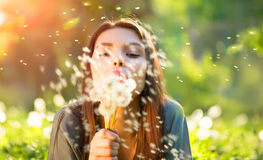 Beautiful young woman blowing dandelions. And smiling Stock Photos