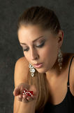 Beautiful Young Woman Blowing Dice for Luck Royalty Free Stock Photos