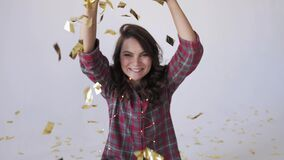 Beautiful young woman blowing gold glitter confetti on a white background