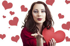 Beautiful young woman  blowing kissed to her valentin. Love and valentines day concep. Beautiful young woman with a gift in a form of heart in her hands blowing Stock Images