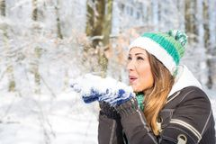 Beautiful young woman blowing snow in the forest. While smiling Royalty Free Stock Images