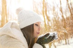 Beautiful young woman blowing snow in the forest stock photo