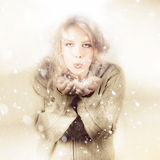 Beautiful Young Woman Blowing Snow In Winter Style Stock Photography
