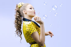 Beautiful young woman blowing soap bubbles Royalty Free Stock Photography