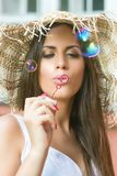 Beautiful young woman blowing soap bubbles outdoor stock photo