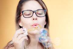 Beautiful young woman blowing soap bubbles outdoors Stock Images