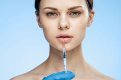 Beautiful young woman on a blue background holds a syringe, plastic, medicine Royalty Free Stock Photos