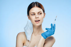 Beautiful young woman on a blue background holds a syringe, plastic, medicine Royalty Free Stock Image