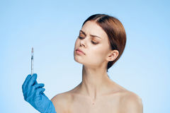 Beautiful young woman on a blue background holds a syringe, plastic, medicine Royalty Free Stock Images