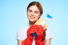 Beautiful young woman on a blue background in rubber gloves, housework, cleaning.  Stock Image
