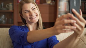 Beautiful young woman in blue blouse sitting on sofa in living room making selfie with smartphone. Beautiful attractive young woman in blue blouse sitting on stock footage