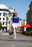 Beautiful young woman in a blue blouse and white skirt walks dow Royalty Free Stock Photography