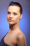 Beautiful young woman with blue creative make-up Stock Photography