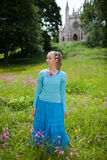 The beautiful young woman in a blue dress in the field at an ancient castle Royalty Free Stock Images