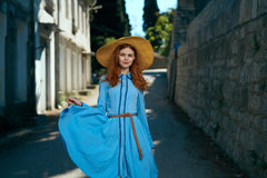 Beautiful young woman in blue dress and hat walking around the city Stock Photography