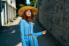 Beautiful young woman in blue dress and hat walking around the city Royalty Free Stock Image