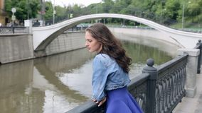 Beautiful young woman in blue dress is standing on a river bank stock video