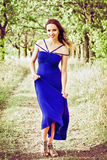 Beautiful young woman in blue dress among the trees Royalty Free Stock Photo