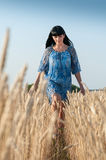 Beautiful young woman in a blue dress. Walk in a wheat field Stock Photography