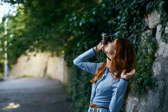 Beautiful young woman in a blue dress walking along the street with a camera Stock Image