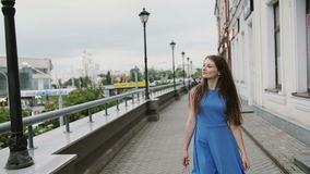 Beautiful young woman in blue dress walking in the city with shopping bags, looks around, slow mo stedicam shot stock footage
