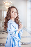 Beautiful young woman in blue dressing gown Royalty Free Stock Photos