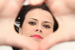Beautiful young woman with blue eyes making heart of fingers Stock Photo