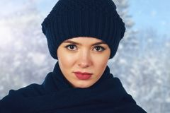Beautiful young woman in blue knitted cap and scarf. Portrait of girl in knitted woolen clothes in winter Stock Photography