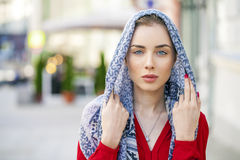 Beautiful young woman in a blue scarf on summer street city Royalty Free Stock Photo