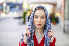 Beautiful young woman in a blue scarf on summer street city Stock Image