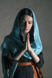 Beautiful young woman in a blue  shawl praying Stock Images