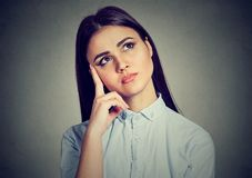 Pensive young woman in doubts stock images