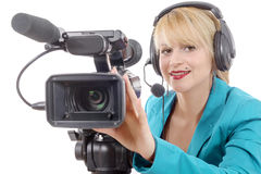 Beautiful young woman with blue suit and professional video came. A beautiful young woman with blue suit and professional video camera Royalty Free Stock Images