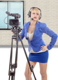 Beautiful young woman with blue suit and professional video came. A beautiful young woman with blue suit and professional video camera Royalty Free Stock Photos