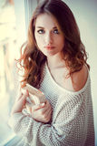Beautiful young woman with book near window Royalty Free Stock Images