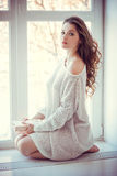 Beautiful young woman with book near window Stock Photos