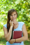 Beautiful young woman with books. Portrait of beautiful young woman with books, against green of summer park Stock Photo