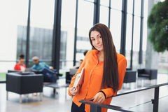 Beautiful young woman with books in college campus. Beautiful young woman holding books under her arms standing by a railing looking at camera. Young caucasian Stock Photography