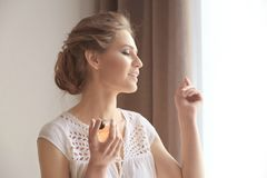 Beautiful young woman with bottle of perfume near window Stock Photography