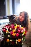 Beautiful young woman with a bouquet of roses and blurred cat. Beautiful woman with a bouquet of roses and blurred cat Royalty Free Stock Photos